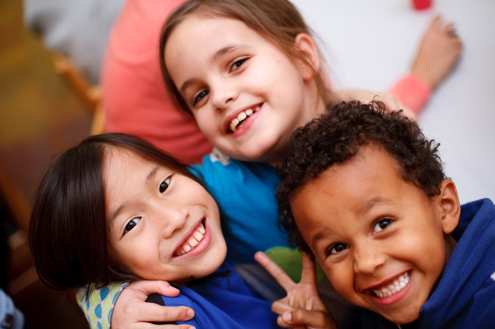Corporate Photo, two smiling girls and one smiling boy looking up at the camera while they are hugging each other.